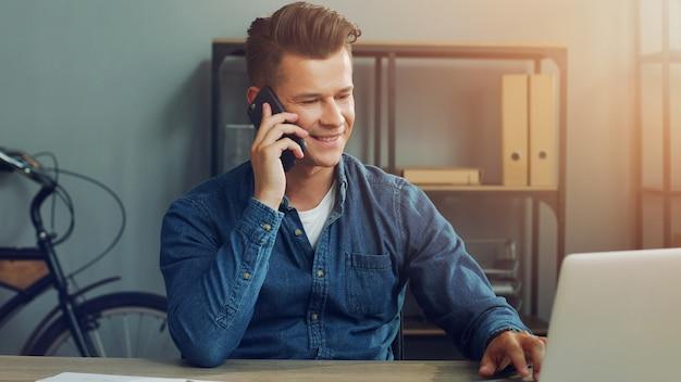 Деловой человек работает в офисе с ноутбуком и с помощью телефона
