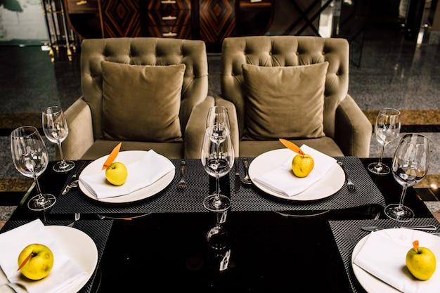 На длинном столе стоит сверкающая стеклянная посуда, приготовленная для свадебного ужина