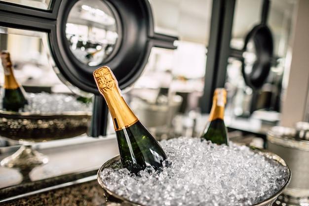 Бутылки шампанского в холодильнике.