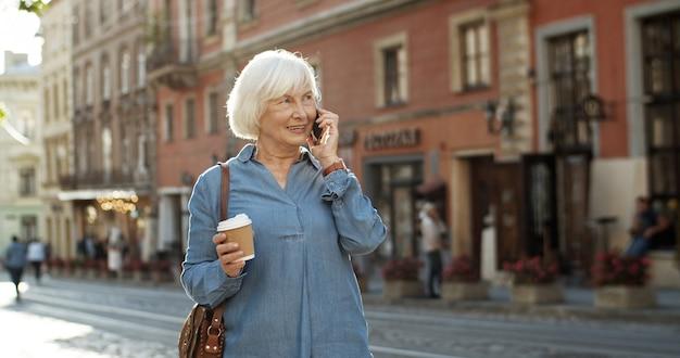 携帯電話で話すブルージーンズシャツの年配の女性