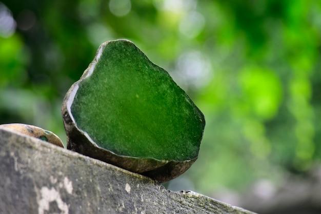 ヒスイは本物の天然のヒスイで、美しい自然の背景に固まります。