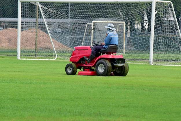 芝刈り機と草刈りの世話をするドライバーとサッカースタジアムは常に見えます