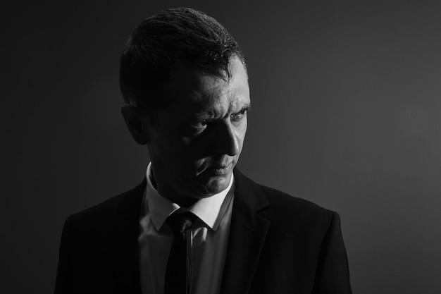 邪悪なボス。怒りのビジネススーツで怒っている男の肖像画。攻撃的な人、黒と白の写真