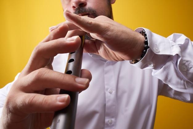 黄色のスタジオでパイプのクローズアップを演奏するプロのミュージシャン男。フォーク管楽器、フルート