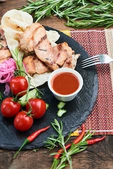 Ужин из жареного бекона и цуккини с соусом цацики на каменной доске