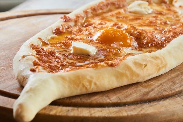 木の板で提供される卵とチーズとアジャラのおいしい伝統的なボート