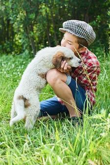 少年は草の上に座っている子犬を抱擁します。