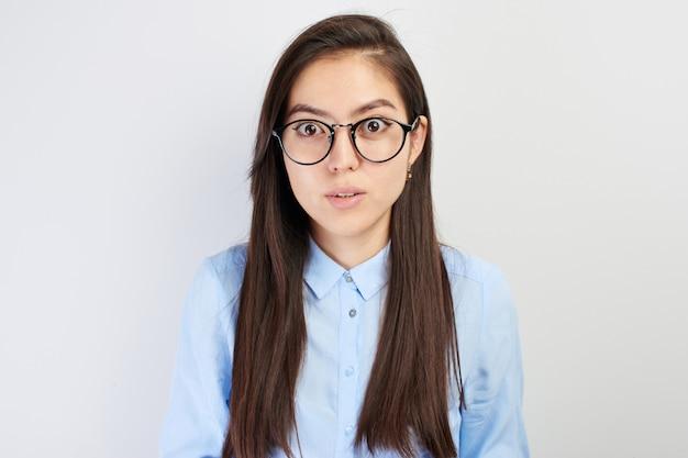 白いスタジオで分離された怖い顔に驚いた肖像画アジアの女の子