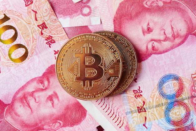 中国元の通貨と暗号通貨ビットコインのクローズアップ。デジタル仮想インターネット通貨投資の概念