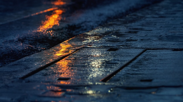 街の雨の夜、アスファルトのレベルからの眺め。