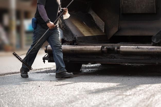 アスファルト道路を修復する道路建設労働者。