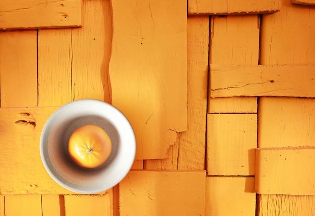 Оранжевый плодоовощ на желтом деревянном поле, желтой предпосылке.