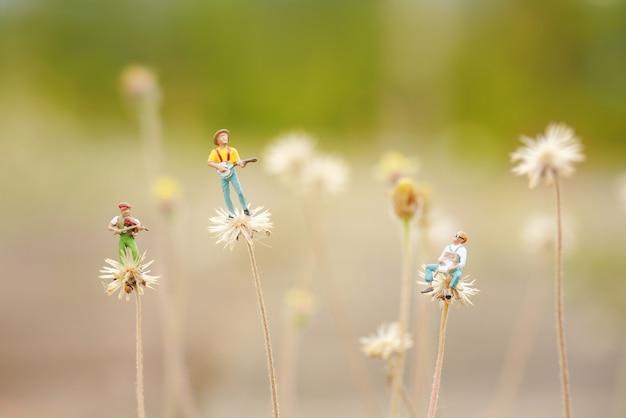 タンポポのような花で音楽を演奏する友人のグループ。ミニチュア、浅い被写界深度、柔らかいパステルカラーのクローズアップ。