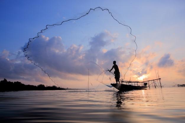 Рыбаки на лодке ловят рыбу сеткой