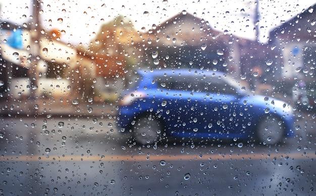 朝の交通、雨の日の風防を通して見る。選択的な焦点と色調。