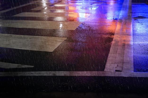 Пешеходный переход (зебра, пешеходная дорожка) на мокрой дороге, дождливая ночь в городе.