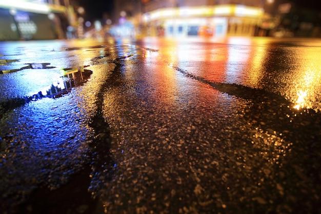 Мокрая дорога, дождливая ночь в городе. вид с уровня асфальта.