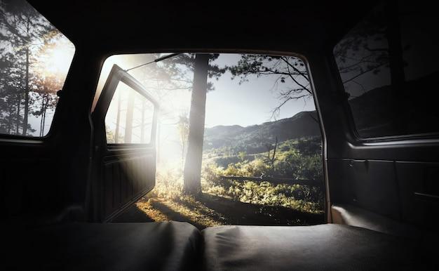 Вид из открытого багажника на вершину горы и сосновый лес.