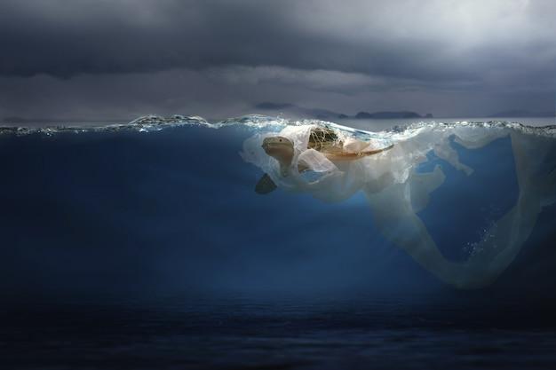 ウミガメ(おもちゃのモデル)がビニール袋のゴミに絡まっています。環境保護とプラスチック意識の概念