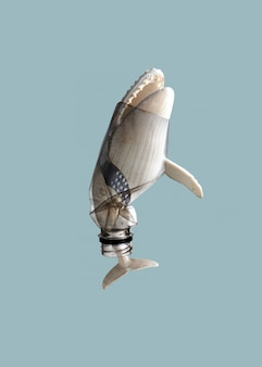ザトウクジラ(おもちゃモデル)の写真で創造的な概念の背景は透明な青いプラスチックボトルで立ち往生し、コピースペースと柔らかいパステルカラーのトーン。