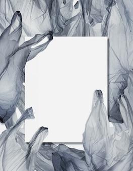 ビニール袋の山に空白のカード。環境保護とプラスチック意識の概念の背景。