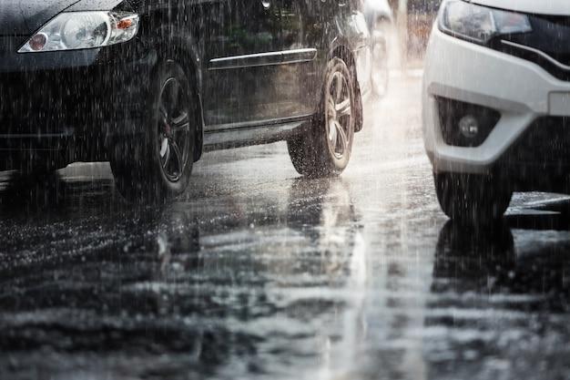 激しい雨がぼやけて車で街に落ちる。セレクティブフォーカスとトーン。
