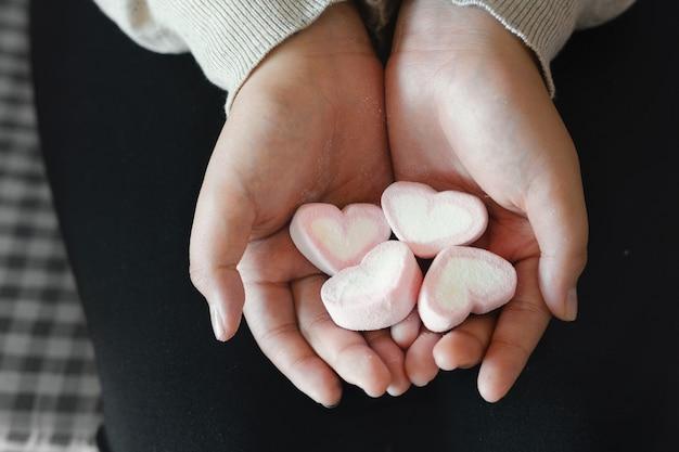 手にハートキャンディーを持つアジアの若い女の子。バレンタインの日。