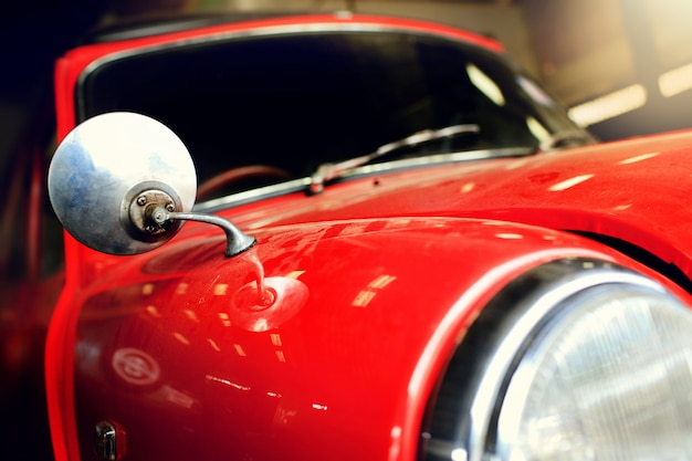 ガレージにほこりが付いている赤いビンテージ車。