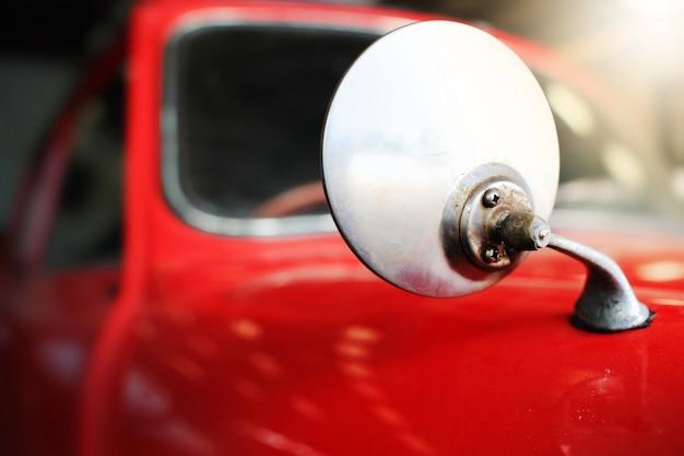 車のミラー、ガレージにほこりが付いている赤いビンテージ車の一部。