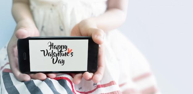 手に携帯電話を持つアジアの少女。バレンタインデーのコンセプト