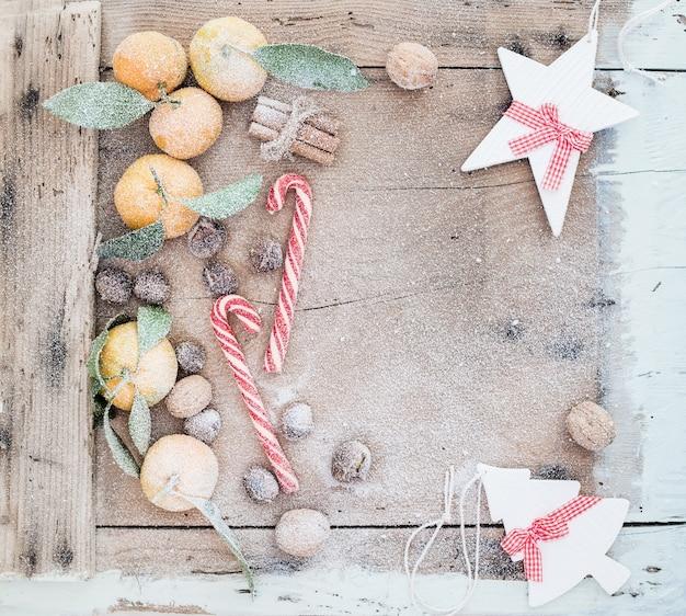 クリスマスまたは新年のフレーム。新鮮なマンダリン、シナモンスティック、クルミ、ロースト栗、キャンディケインは素朴な木製のテーブルの上に雪で覆われています