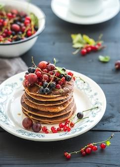 朝食セット。新鮮なベリーと黒の木製テーブルの上の素朴なプレートに蜂蜜のそばパンケーキ。