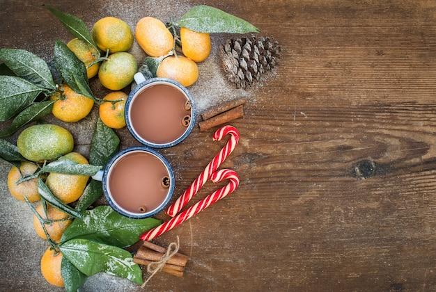 クリスマスまたは新年のフレーム。素朴な木製、トップビューで葉、シナモンスティック、松ぼっくり、マグカップやキャンディー杖でホットチョコレートと新鮮なみかん