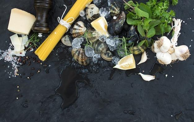 スパゲッティボンゴレを調理するための材料。砕いた氷、生パスタ、パルメザンチーズ、ニンニク、パセリ、レモンの石スレート、トップビューでアサリ