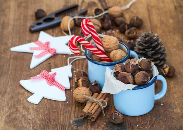 伝統的なクリスマス料理と装飾。ロースト栗、ブルーエナメルマグカップ、クルミ、シナモンスティック、キャンディー、素朴な木製の松ぼっくり