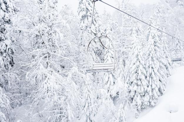 雪が降った後、モンテネグロのコラシンの町の近くの針葉樹林のマウンテンスキーリゾートを通過する乗客のいない古いケーブルリフト