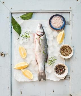 レモン、ハーブ、氷、素朴な青い木の板にスパイスと新鮮な調理シーバス魚