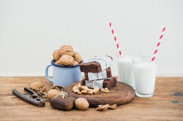 紙に包まれ、ロープ、ミルクグラス、ストライプストロー、素朴な木製のテーブルにクルミのエナメルマグカップで疲れてチョコレートブラウニースライス