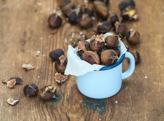 素朴な木製、選択的な焦点に青いエナメルマグカップで焼き栗。