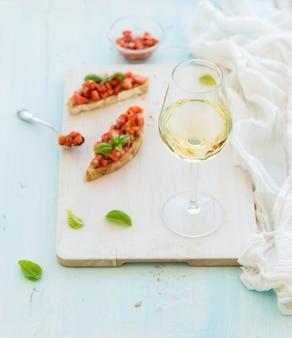 塗られた木製のサービングボードに白ワイン、トマト、バジルのブルスケッタサンドイッチのガラス