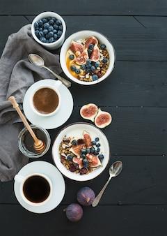 健康的な朝食セット。オーツ麦グラノーラとヨーグルト、新鮮なブルーベリーとイチジク、コーヒーと蜂蜜のボウル