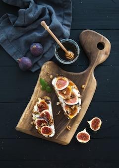 リコッタチーズ、新鮮なイチジク、クルミ、素朴な木の板に蜂蜜のサンドイッチ