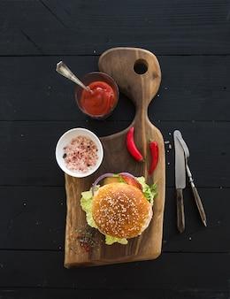 Свежий домашний бургер на темной сервировочной доске с острым томатным соусом и морской солью