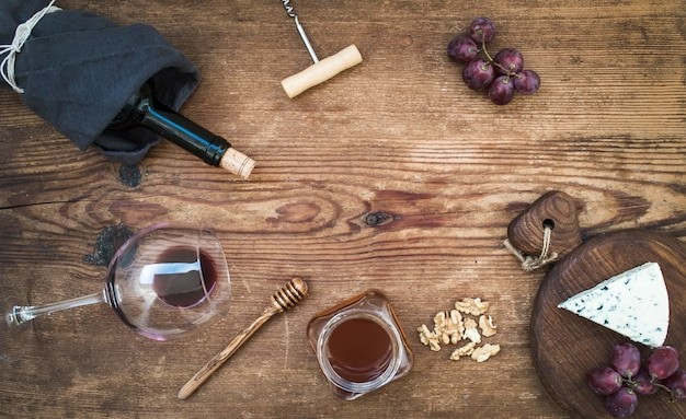 Вино и закуска с копией пространства в центре. стакан красного вина, бутылка, штопор, голубой сыр на сервировочной доске, виноград, мед, грецкие орехи на деревенский деревянный столик, вид сверху.