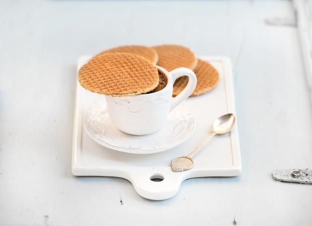 オランダのキャラメルストロープワッフルとライトブルーの木製の表面上の白いセラミックサービングボード上のブラックコーヒーのカップ