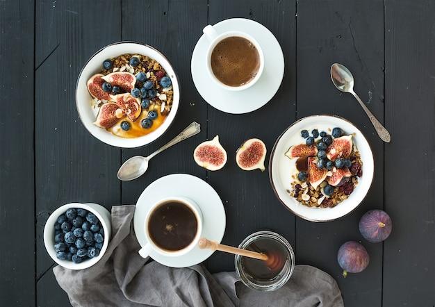 健康的な朝食セット。エンバクグラノーラヨーグルト、新鮮なブルーベリーとイチジク、コーヒー、蜂蜜、黒の木製テーブルの上
