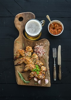 Жареные куриные крылышки на деревенской сервировочной доске, острый томатный соус, зелень и кружка светлого пива