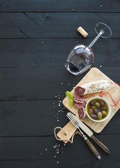 ワイン前菜セット。赤ワイン、フレンチソーセージ、黒の木製テーブルにオリーブのガラス