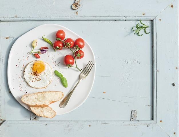 朝食セット。目玉焼き、パンのスライス、チェリートマト、唐辛子、ハーブの白いセラミックプレート