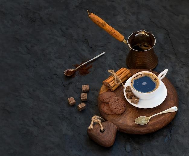 チョコレートビスケット、シナモンスティック、素朴な木の板に砂糖キューブとブラックコーヒーのカップ
